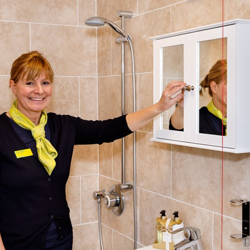 lady opening medicine cabinet in wet room for care home